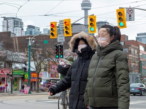 Women in downtown Toronto's Chinatown wear protective masks on Jan. 27, 2020.