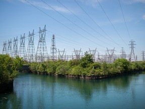 Power lines hang from transmission pylons above a reservoir at the Ontario Power Generation Inc. Sir Adam Beck Generating Station along the Niagara River in Niagara Falls, Ontario.