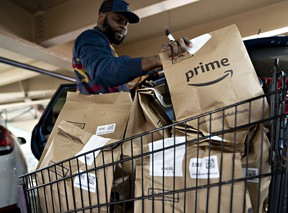 An independent contractor picks up an Amazon.com Inc. Prime grocery bag outside a Whole Foods Market Inc. store in Washington, D.C.