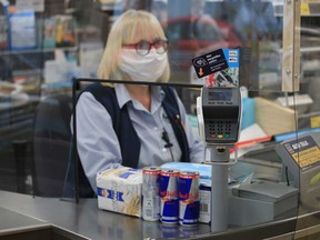 An cashier serves a customer behind a plastic shield to prevent the spread of coronavirus disease.