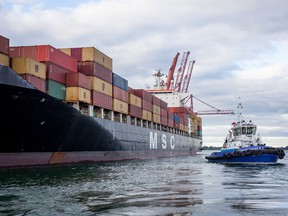 A tugboat helps a cargo ship dock at the Port of Montreal.
