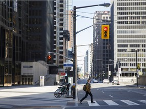 A pedestrian crosses Bay Street in Toronto's financial district.