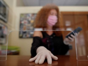 A worker wearing a face mask and gloves is seen behind a protective screen in an office. Opening up the economy is proving a delicate dance for workplaces.