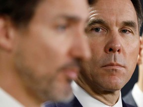 Finance Minister Bill Morneau, right, seen with Prime Minister Justin Trudeau, will provide a fiscal update Wednesday that's expected to show a current-year deficit of at least $250 billion.