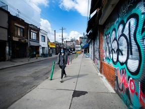 A person walks by a closed business in the Kensington Market neighbourhood of Toronto in April.