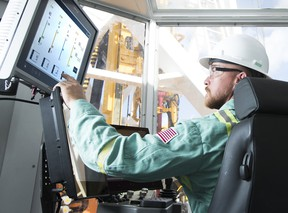 A Precision Drilling tech worker examines drilling data at the Houston Technical Service Center.