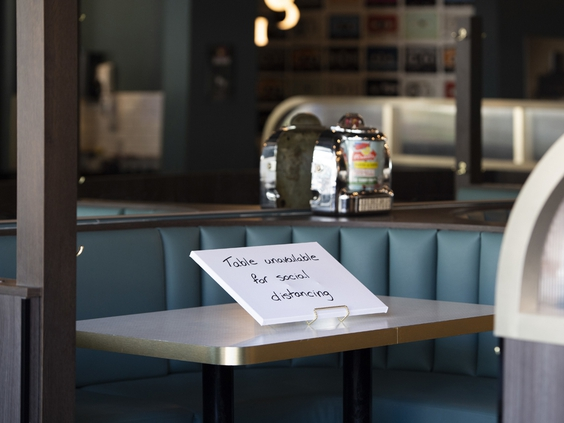 A social distancing sign is displayed at booth in a restaurant on the first day of indoor dining in Ottawa, in July.