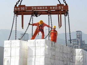 Workers load products for export onto a ship at the port in Lianyungang, in China's eastern Jiangsu province.