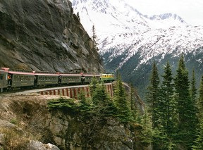 A White Pass and Yukon passenger train rounds a curve on the narrow-gauge track as it descends through the mountains to Skagway, Alaska.