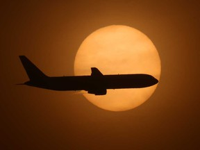 A cargo plane on its final approach into Long Beach Airport passes in front a hazy sun caused by smoke from a wildfire that covered 4,000 acres and forced the evacuations of 60,000 residents.