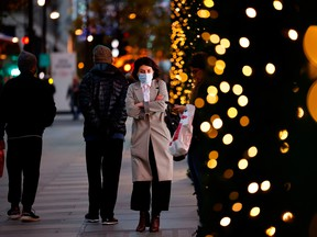 A pedestrian walks past a Christmas-themed window display at a department store in London.