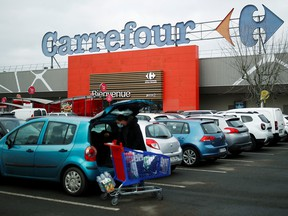 A customer empties his cart in front of a Carrefour hypermarket store in Carquefou near Nantes, France January 13, 2021.