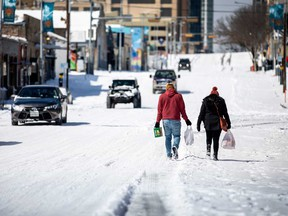 People carry groceries from a local gas station on Monday in Austin, Texas. Winter storm Uri has brought historic cold weather to Texas, causing traffic delays and power outages.