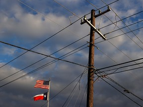 The U.S. and Texas flags fly next to a power pole in Houston, Texas.