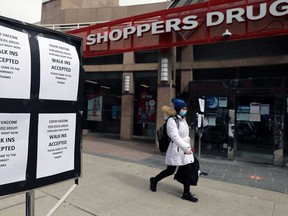 A woman wearing a face mask walks past a Shoppers Drug Mart store advertising coronavirus vaccines, in Toronto. Despite a second lockdown, the economy showed surprising strength.
