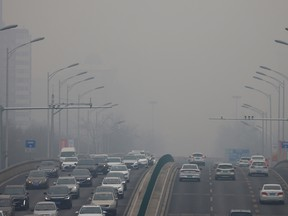 Cars move on a road during a day with polluted air in Beijing, China, February 13, 2021.