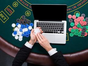 A close up of poker player with playing cards, laptop and chips at green casino table.