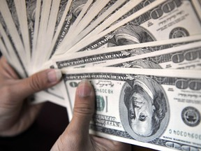 A money changer counts out U.S. 100-dollar banknotes