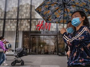 People walk by an H&M clothing store at a shopping area on March 30, 2021 in Beijing, China.