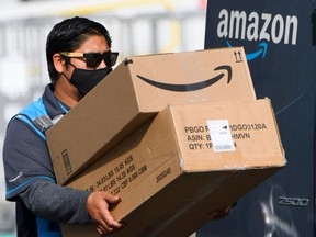 An Amazon delivery driver carries boxes into a van outside of a distribution facility in Hawthorne, California. Amazon.com Inc. is pausing plans for its annual sale Prime Day in Canada and India due to concerns about COVID-19. The pause won't affect Prime Day in the U.S.