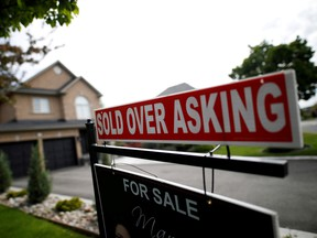 """A real estate sign that reads """"For Sale"""" and """"Sold Above Asking"""" stands in front of housing in Vaughan, Ont."""