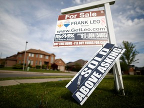 """A real estate sign that reads """"For Sale"""" and """"Sold Above Asking"""" stands in front of housing in Vaughan, a suburb in Toronto."""