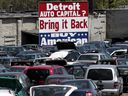 A 'Buy American' sign, in support of Detroit's auto industry, is seen in the back of an auto scrap yard in Detroit, Michigan in 2009. Automotive manufacturing is likely to see the most significant changes in a century as batteries and motors gradually replace conventional engines that combust gasoline during the next decade.