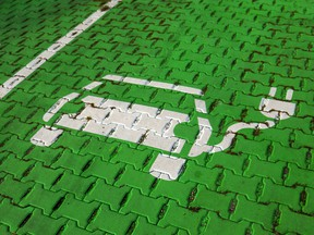 An electric car stencil symbol sits on a parking space at an electric vehicle charging site