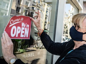 A shop owner places an open sign on her store window. Canadian businesses say they're expecting inflation to get worse.