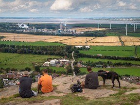 Walkers look out from Helsby Hill across the Mersey Estuary towards the CF Industries Holdings Inc. fertilizer manufacturing complex, which is being forced to be shut down due to high natural gas prices, in Ince, U.K.