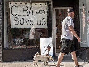A store in Toronto displays a sign saying 'CEBA Won't Help Us' during the COVID-19 pandemic. A recent Equifax Canada survey found that most small business owners do not feel supported by their banks and government.