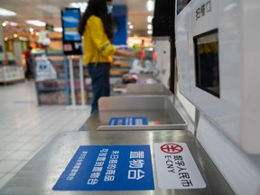 Signage for the digital renminbi, also referred to as E-CNY, at a self check-out counter inside a supermarket in Shenzhen, China.