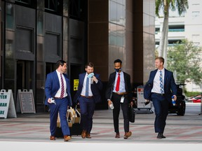 Pedestrians walk outside the Palm Beach County Courthouse in West Palm Beach, Florida. Wall Street firms are expanding in South Florida.