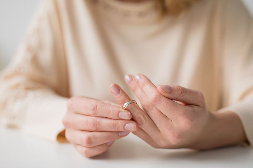 woman's hands taking ring off