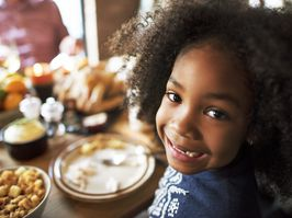 young girl smiling over a thanksgiving feast