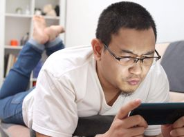 Young Asian man lying on cozy sofa, playing games on his smart phone, happy leisure activity