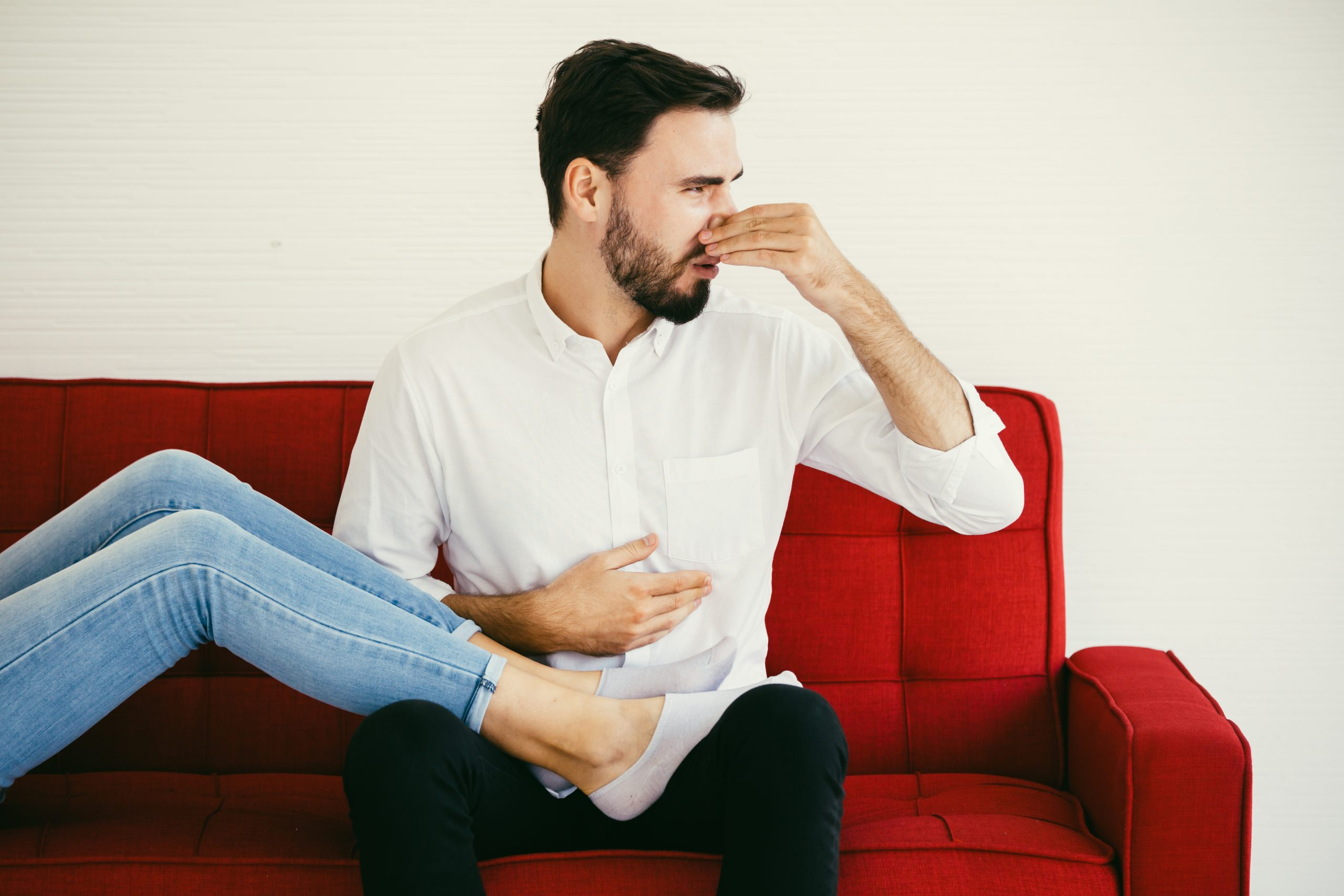 man holding nose with woman's feet in his lap