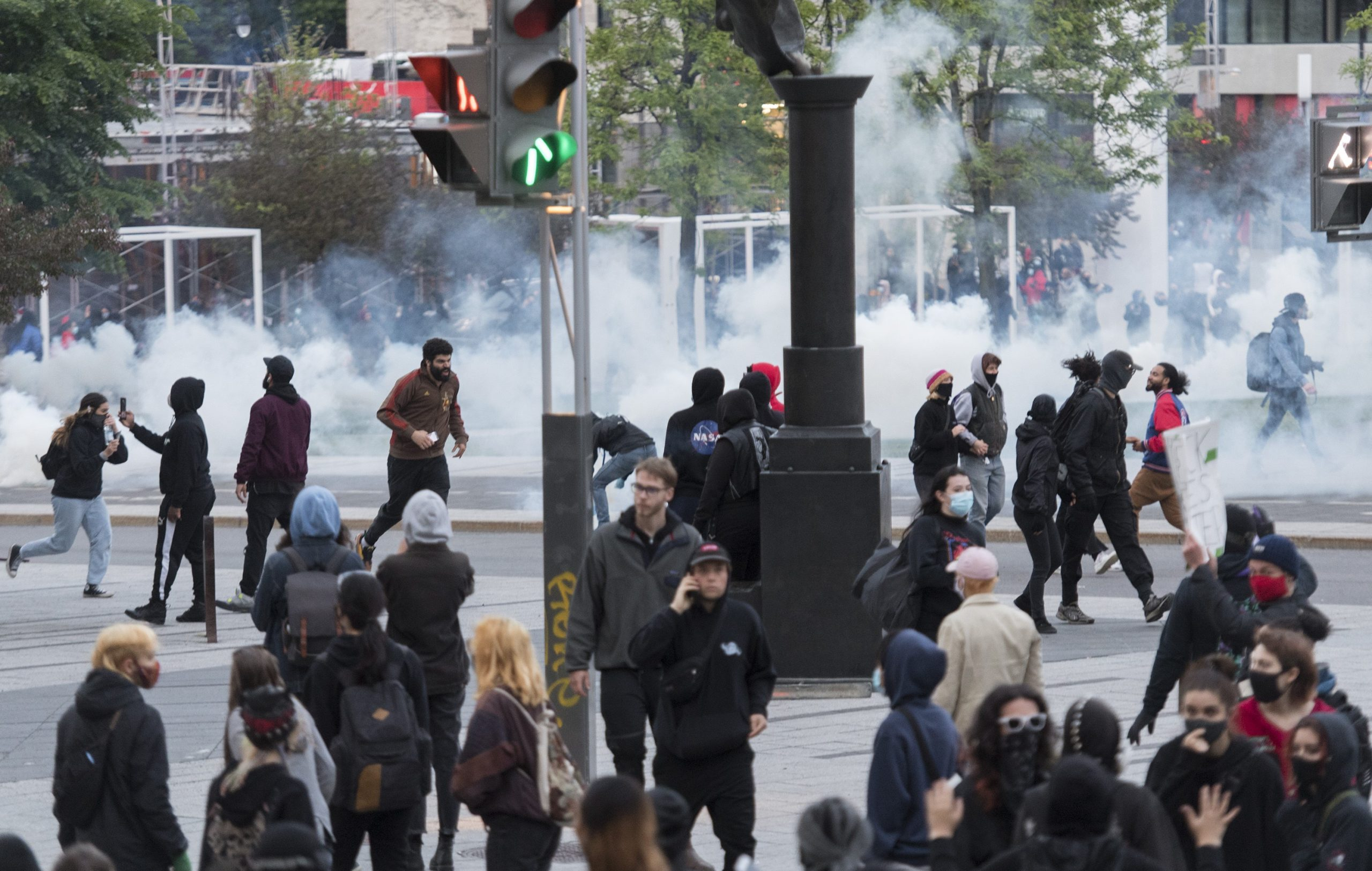 Protestors run from tear gas in Montreal
