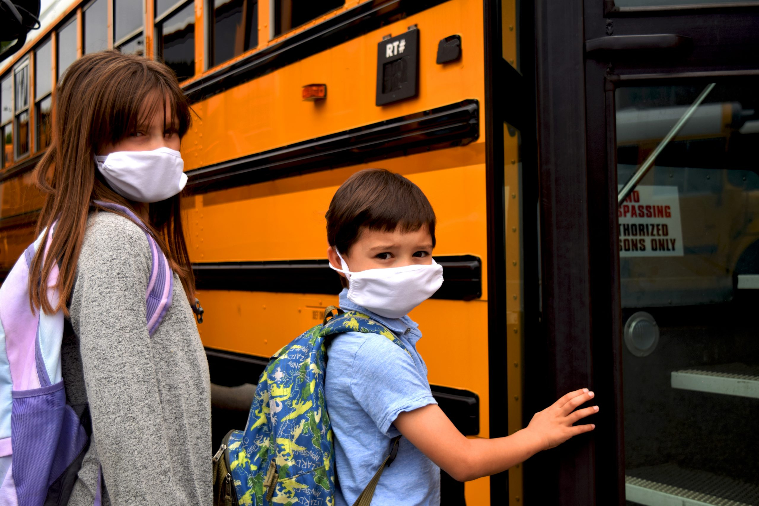 two kids getting on a school bus wearing masks