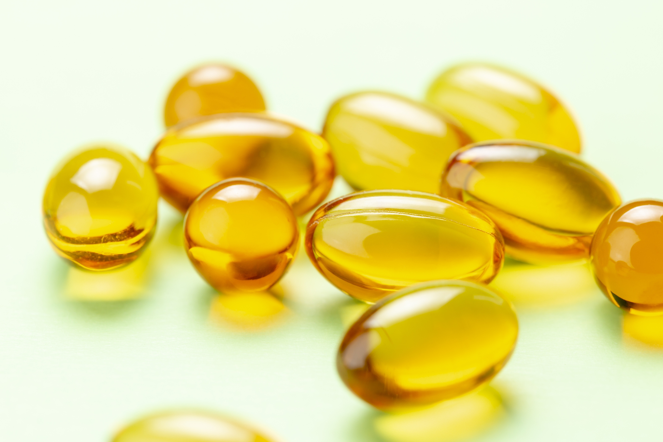 Close up of Vitamin D3 Omega 3 fish oil capsules on green background