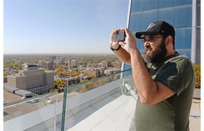 Derek Jaworski snaps a pic of the city from the roof of Hill Tower III during a Doors Open event in Regina, Sask. on Saturday Sep. 26, 2015. An initiative of the Regina Downtown Business Improvement District, the activities give the public a chance to experience the city's downtown buildings and heritage. (Michael Bell/Regina Leader-Post)