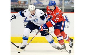 Isaac Schacher (L) with the Saskatoon Blades fights for the puck with Austin Wagner (R) with the Regina Pats during WHL hockey at the Brandt Centre in Regina on Oct 31, 2014.