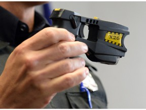 A Regina Police Service member holds a Taser, also known as a conducted energy weapon.