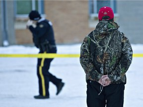 A man holds a rosary as police investigate the scene of the shootings at the community school in La Loche.