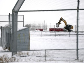 A trackhoe works on the demolition of Pacer Park ball diamonds in Regina on Monday.