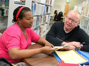 Learner Aline Nizigama (L) from Burundi with tutor Gene Josephson (R) at the Regina Public Library in downtown Regina.  Despite a recent influx of tutors, some learners have been waiting two years for a tutor.