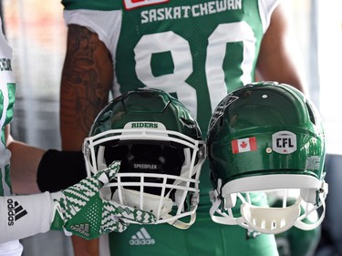 Matt Webster and Spencer Moore show off the new helmets at the launch of the new Saskatchewan Roughriders adidas uniforms for the 2016 season. The black trim was removed from the jersey and the numbers and the pants feature four stripes on the left side – each one representing a Grey Cup victory over the years.
