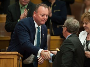 Saskatchewan Finance Minister Kevin Doherty shakes premier Brad Wall's hand after delivering the budget speech on June 1.