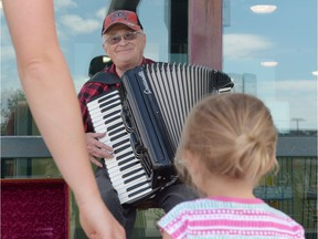 """Dan """"The Accordian Man"""" Petrie smiles while playing outside the Quance Street liquor store in Regina, Sask. on Sunday."""