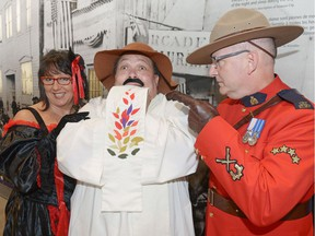 """Jackie Senko as """"Klondike Kate"""", Andrew Waithe as """"The Good Padre"""" and Cpl. Dan Toppings in the role of a North-West Mounted Police officer pose at the RCMP Heritage Centre in Regina. The trio were promoting The trio were promoting A Night in the Museum – Murder in the Klondike, a murder mystery costume gala fundraising event on Oct. 22 to support The Caring Place and the RCMP Heritage Centre."""